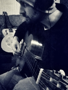 Studio Shot 3 - Playing my dad's old nylon string guitar. Taken by Chris Hollis